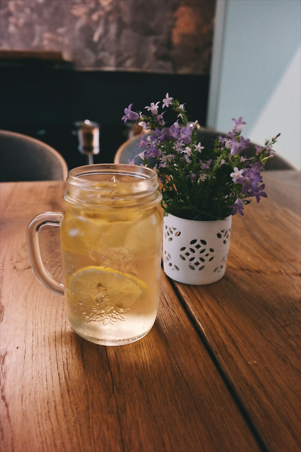 glass with lemons on a wood table with purple flowers