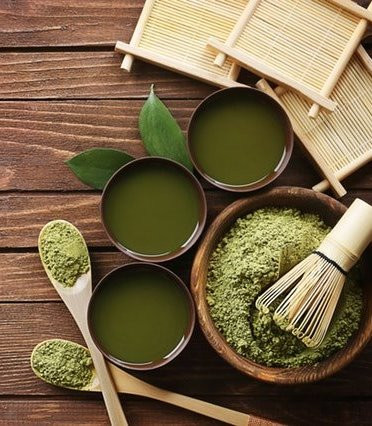 matcha green tea powder and cups with wooden spoons