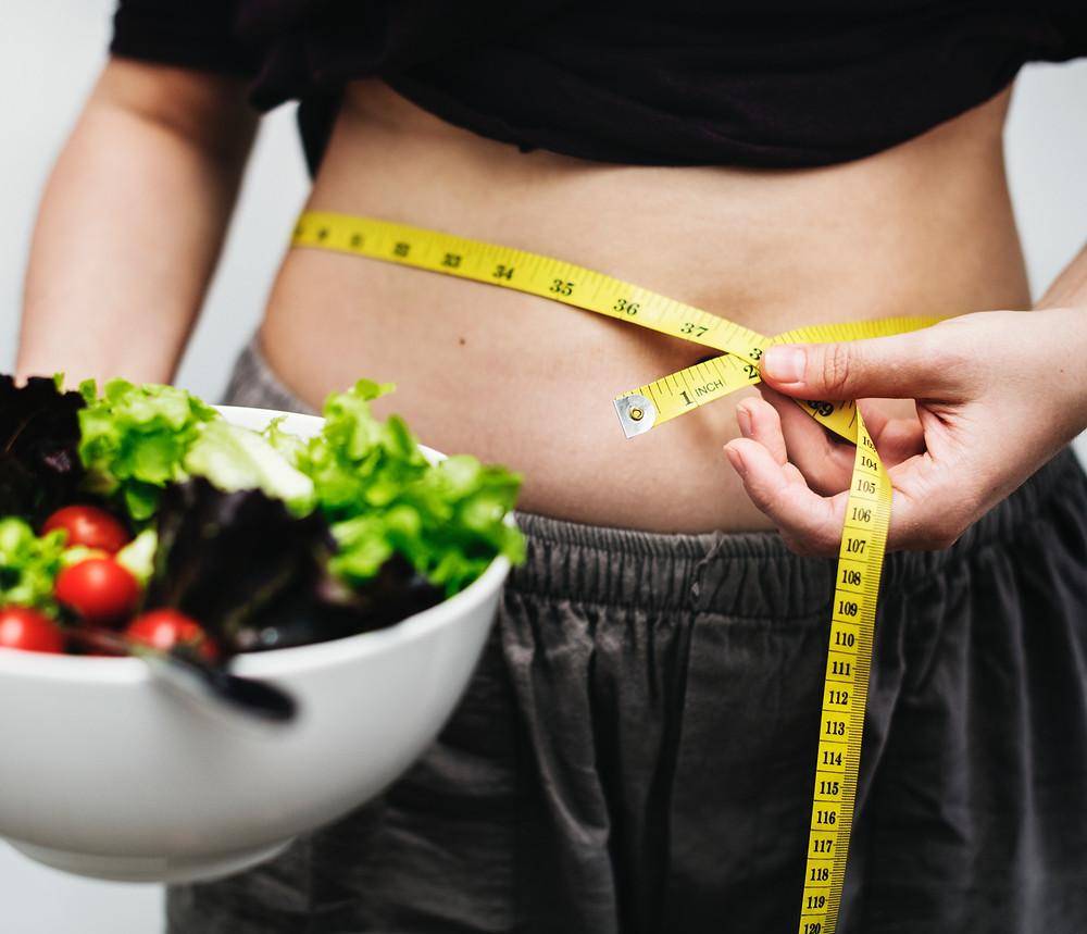 woman measuring waist salad bowl tape measure