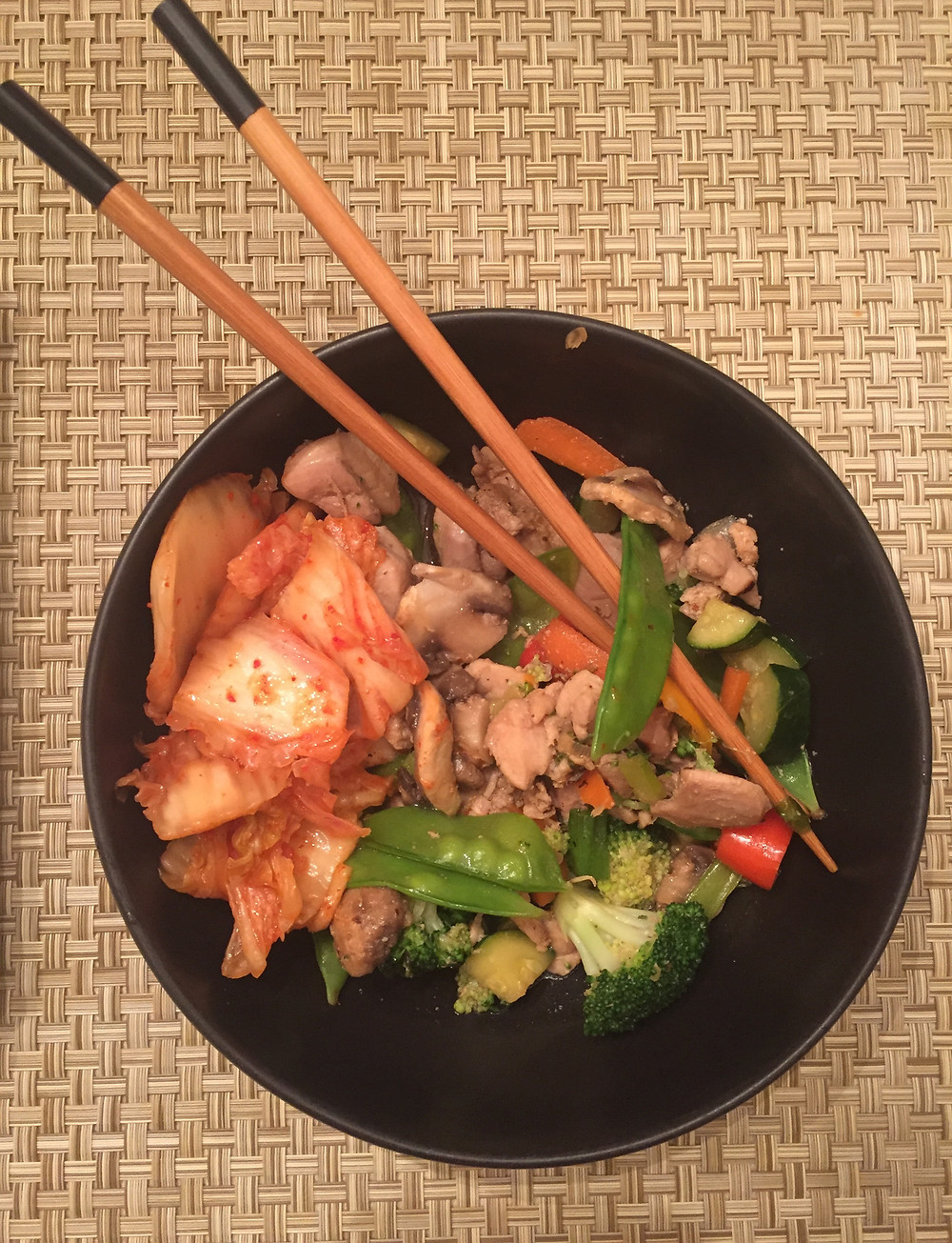 plate of chicken stir fry with mixed vegetables chop sticks kimchi