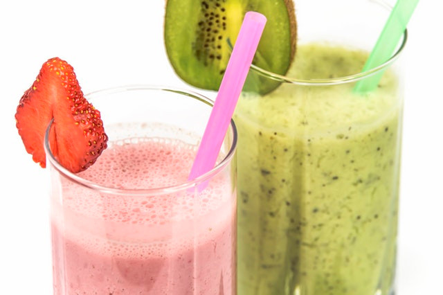 Fruit smoothies in glasses with strawberry and kiwi green and pink