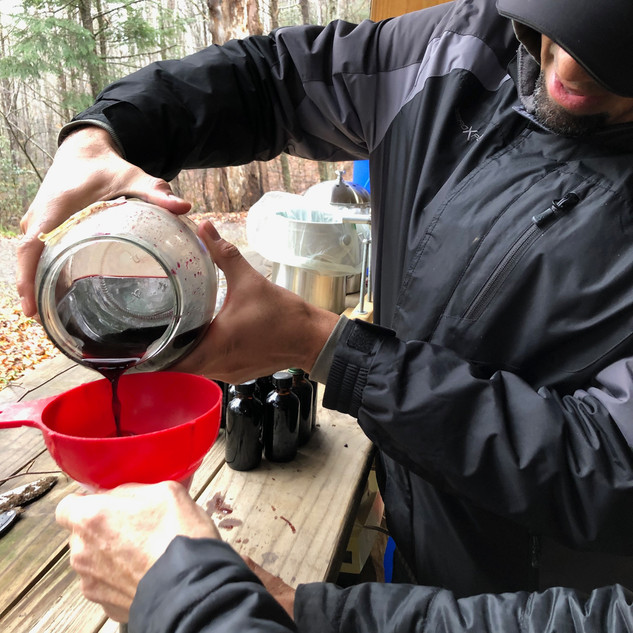 Pouring the Elderberry Syrup into Bottles