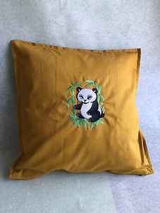 mustard coloured cushion with a giant panda embroidery