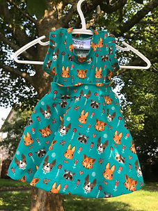 Turquoise children's dress with small animal faces on it.