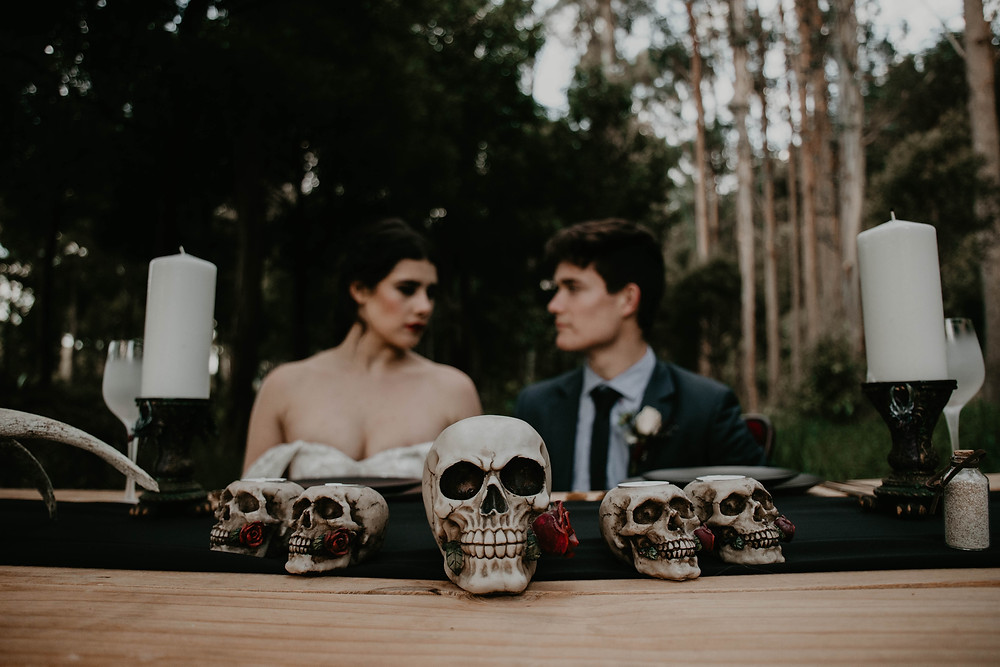 Vintage Halloween inspired wedding styled shoot, skull reception table framed by pillar candles.
