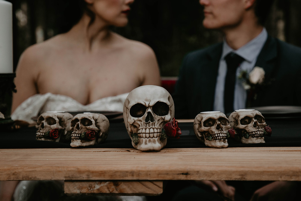 Halloween inspired shoot with wedding couple sat at table of skulls.