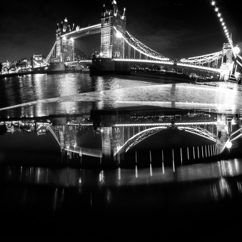 Reflections -  A Curved View Of A Bridge
