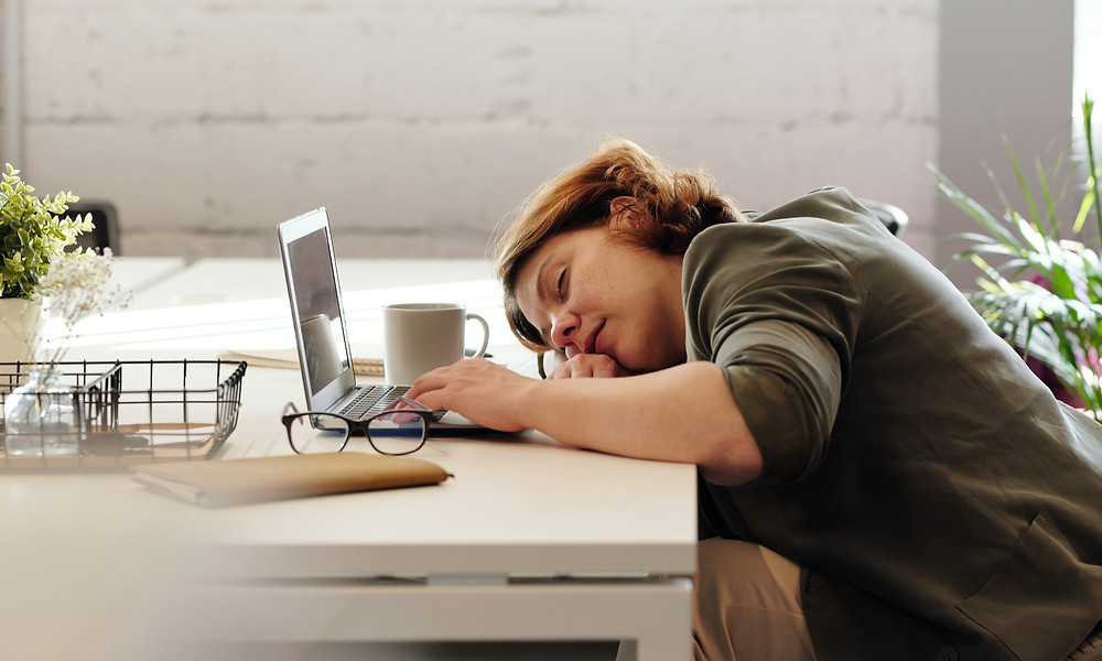 Fatigued woman sleeping on desk with laptop and glasses