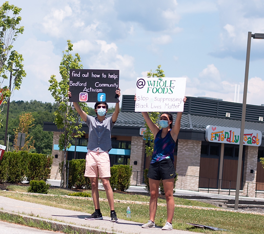 Daniel and his friend holding signs that says Bedford Community Activism