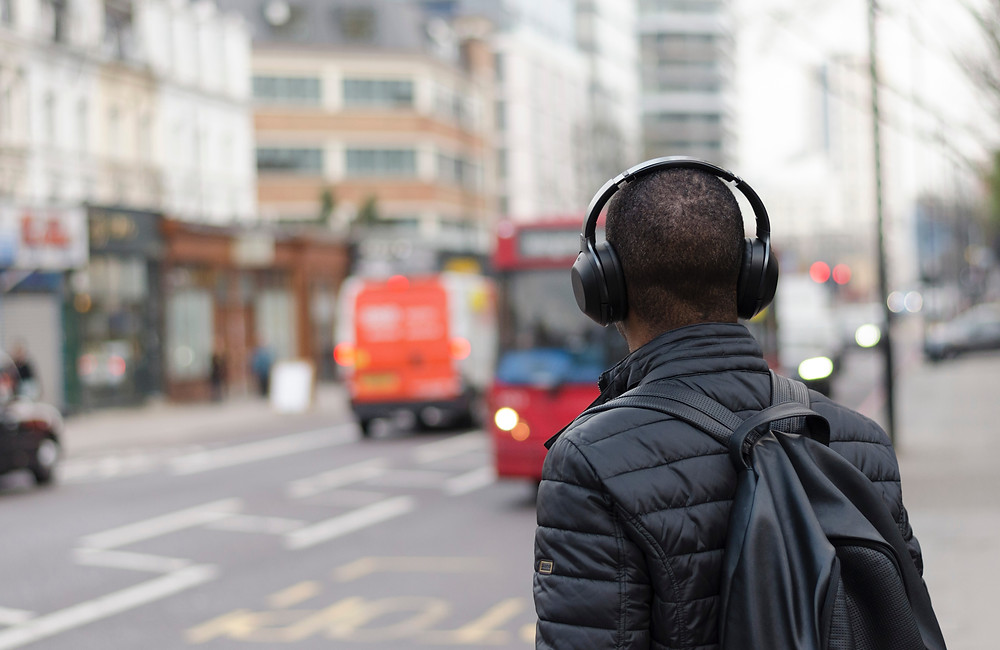 Man listening to wireless headphones on sidewalk near busy street