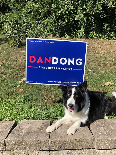 Dan's dog Cookie in front of a Dan Dong sign