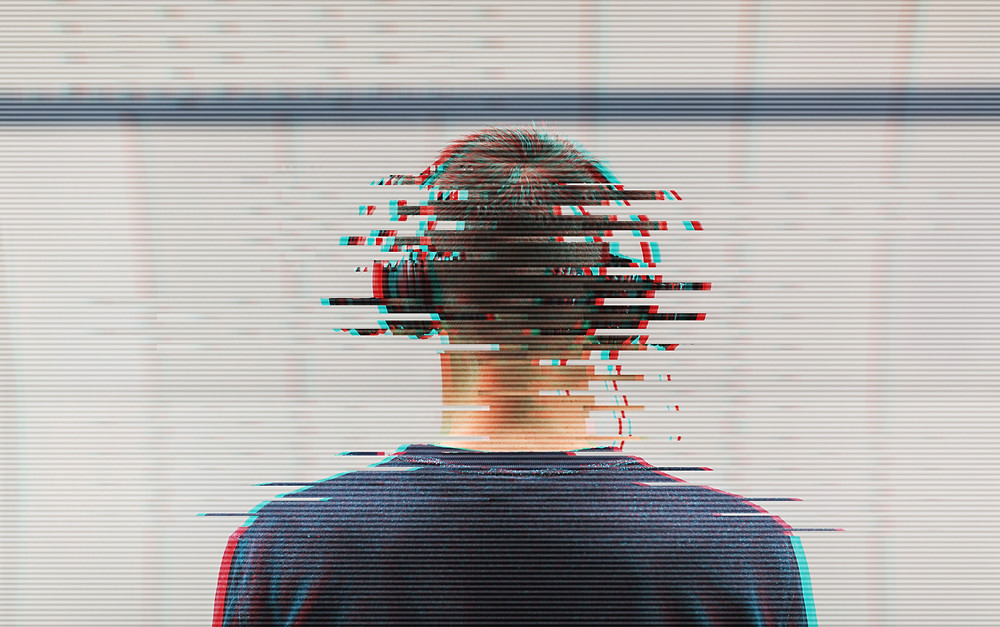 Very glitchy image of man listening to headphones.