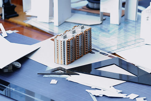 architect-construction-engineer-desk-with-drafting-tools-and-schematics-and-3D-model-of-three-high-rise-apartment-buildings