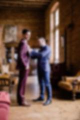 le témoin accroche la boutonnière au marié dans son costume bordeaux