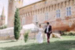 Couple de jeune mariés marchant dans les jardins du château