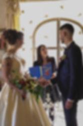 Crémonie laïque le couple de mariés s'unissant devant l'officiante de cérémonie et un riedeau de fleurs en papier