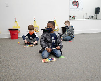 Students playing small xylophones