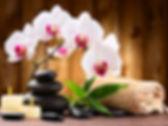 cadre parfumé par une bougie posé au pied d'un branche de sakura et de bambou accompagné de pied d'eau douce et d'une serviette.