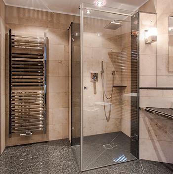 Detailansicht Dusche mit Pendeltürband von MWE und hochglanzpolierte Edelstahl Heizkörper