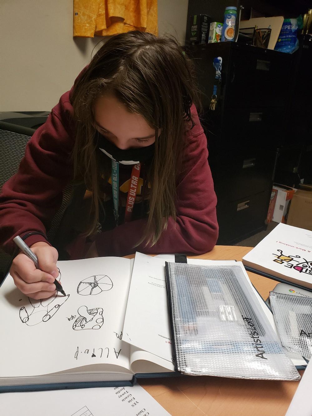 Girl draws in sketchbook
