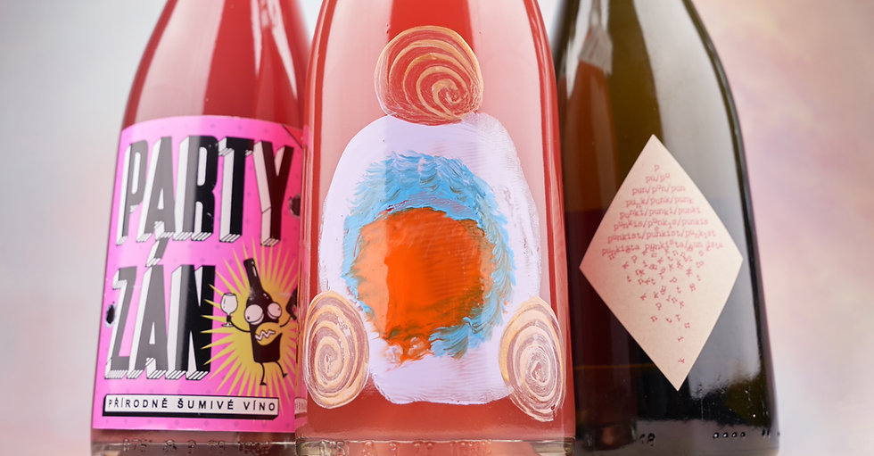 """Three colourful bottles of natrually sparkling wine, all with unique labels. One bottle includes an illustration of a drunk wine bottle, one is a special edition hand painted bottle and one has a lable with the word """"punkista"""" repeated many times, slowly disintegrating."""