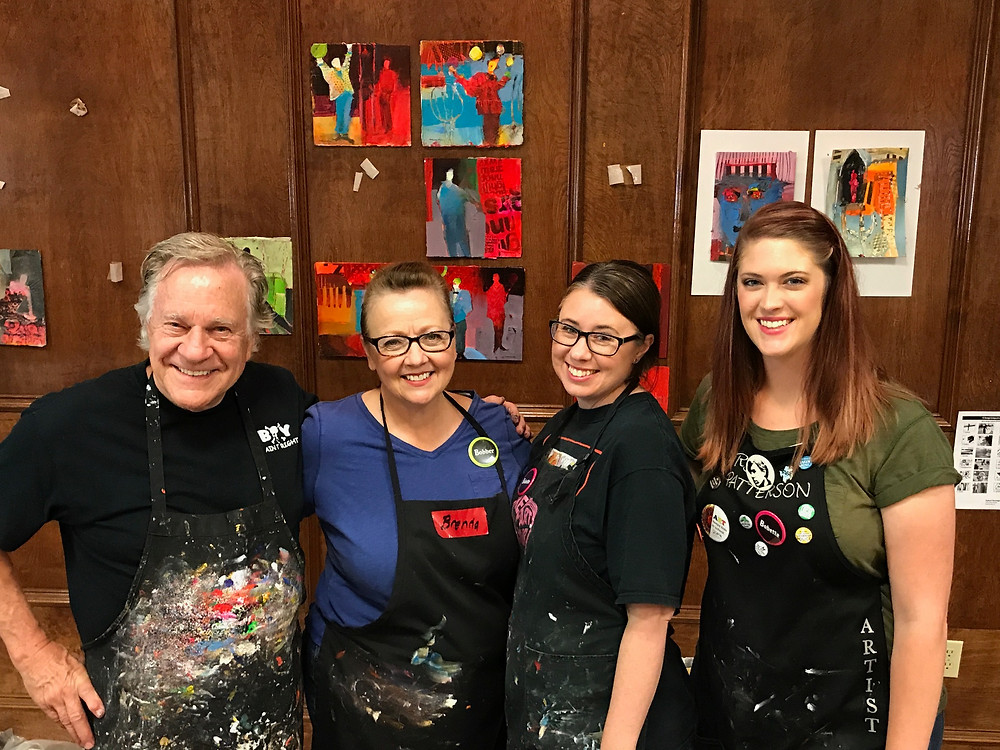 One man and three women smiling in art studio