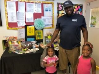 Adult smiling with two children in classroom