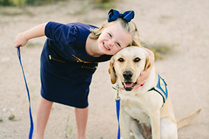 Young girl smiling with yellow labrador retriever guide dog