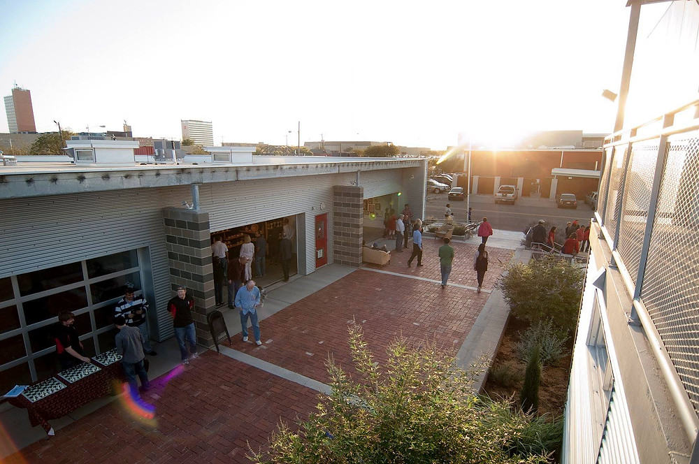 People walking around the Charles Adams Studio Project buildings during a sunset