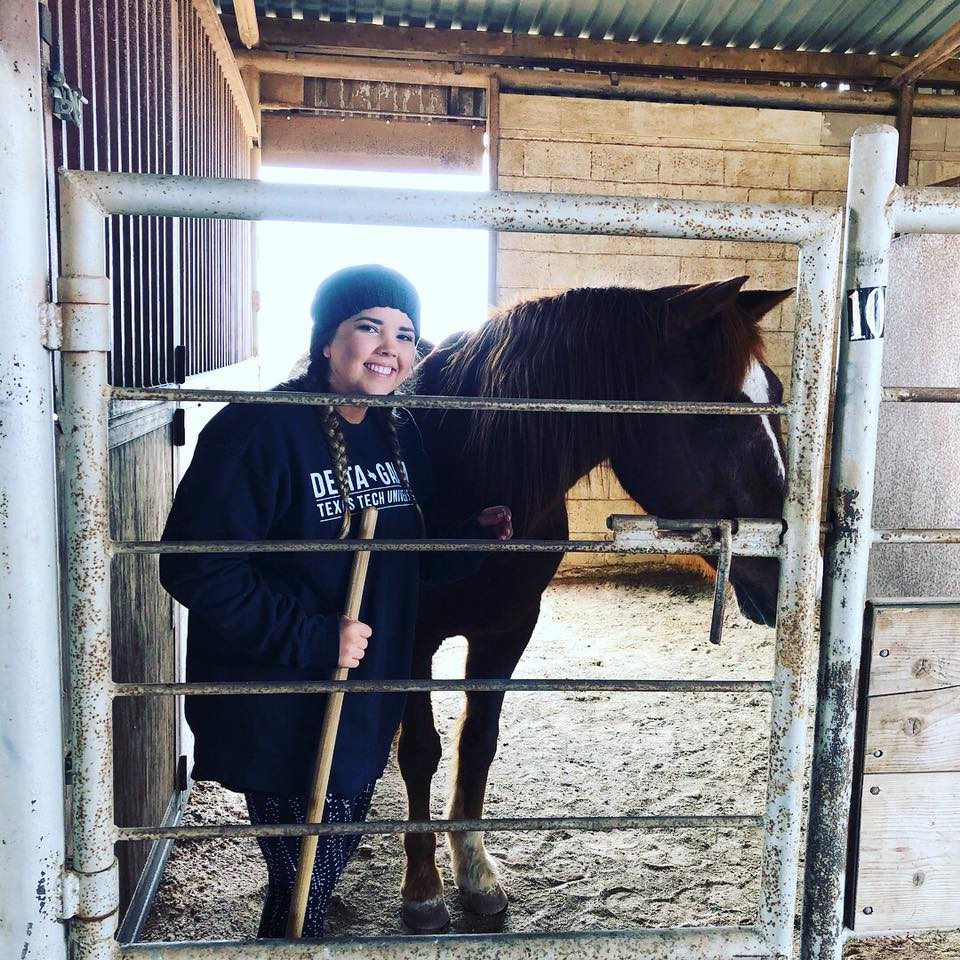 Volunteer in stable with horse