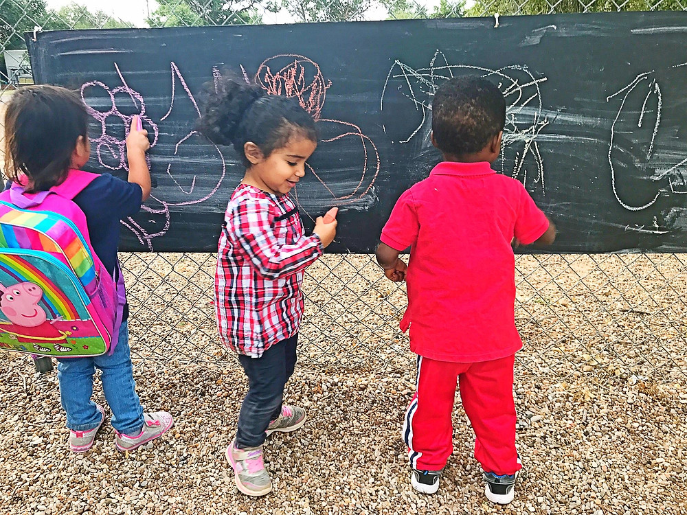 Children drawing on an outdoor chalkboard