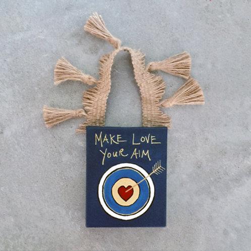 """""""Make Love Your Aim"""" Door Hanger"""