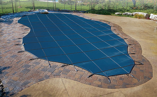 A blue safety cover on top of an inground pool