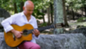 Int'l Fingerstyle Guitar Champion Mark Sganga playing his acoustic guitar in Harriman State Park