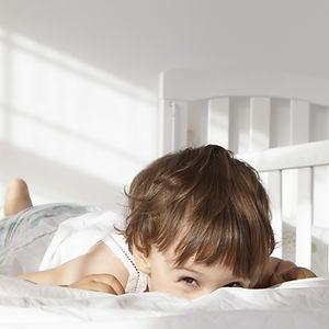 Jeune garçon avec les yeux rieurs, allongé sur le ventre.