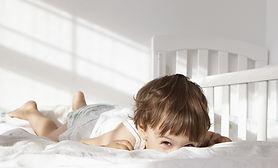 Niño que mira a escondidas sobre la cama