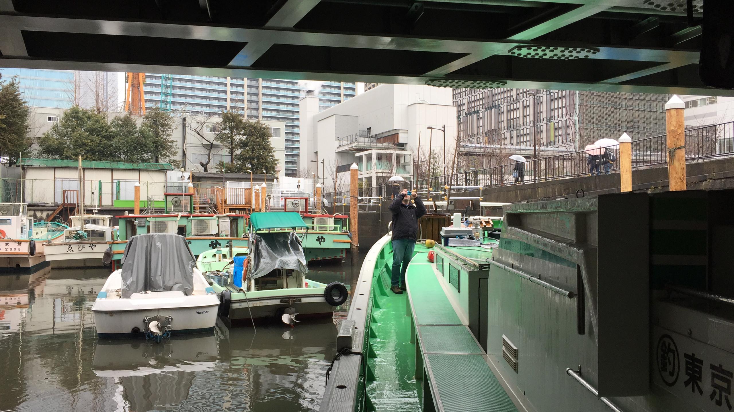 Charter vessel underway clearing a low bridge in downtown Tokyo