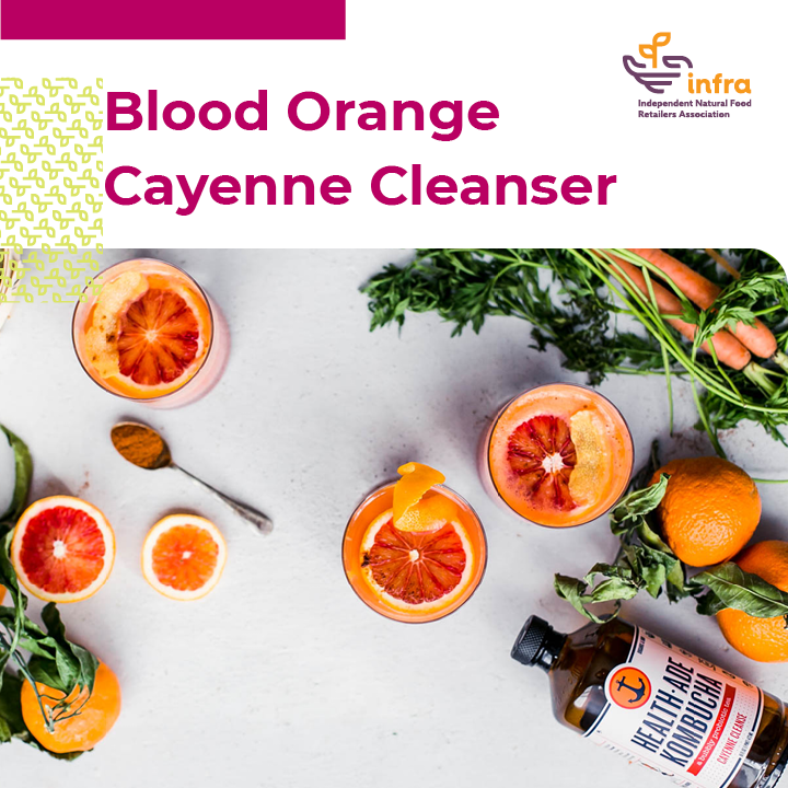 drinks with orange slices, carrots, greens, whole oranges, Health Ade bottle, and spoon of cayenne spread across a white background