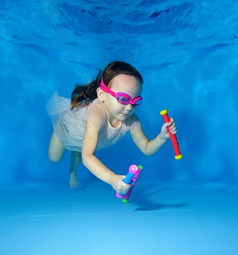 Little girl swims underwater and picking up toys from the bottom of the pool on a blue bac...ted.jpg
