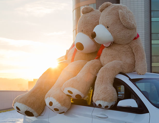 Giant teddy bears with red ribbons sitti