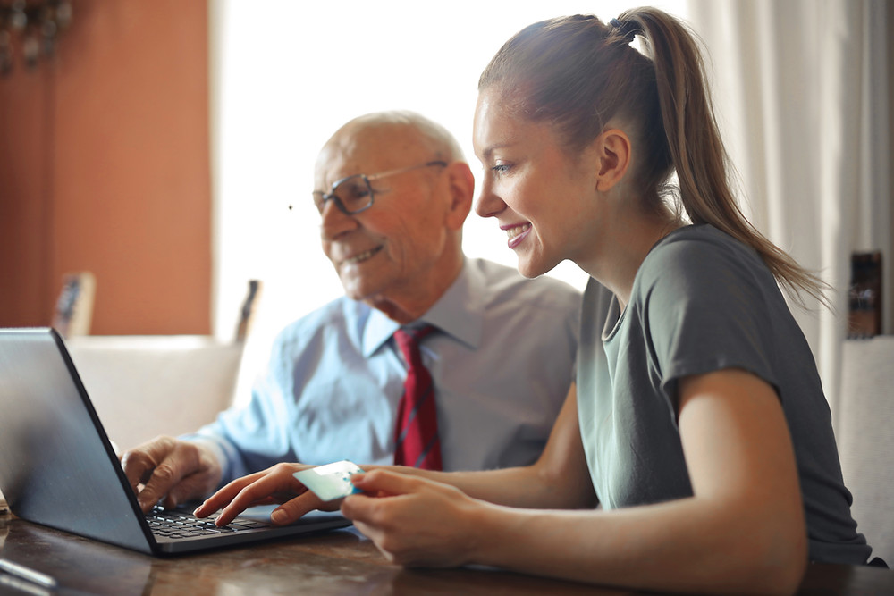 Young woman working with older male on creating a funeral trust