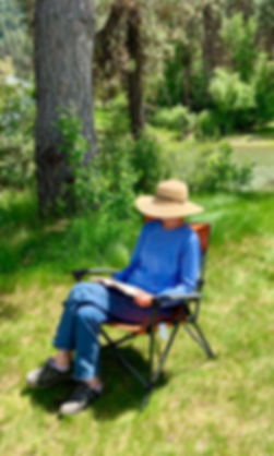Author, Laurie Buchanan, sitting in a chair by a river reading a book