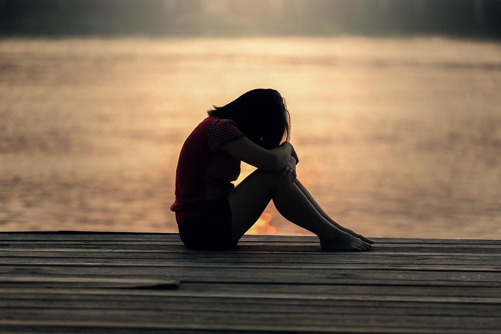 mulher sentada chorando, mulher sentada triste, mulher com a cabeça abaixada, Milene Oliveira, Dança Cristã