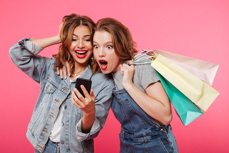 shocked-two-women-friends-holding-shoppi