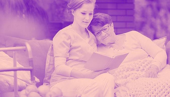 A nurse reading a book to a patient