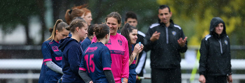 Young women laughing on rain break in soccer game male coach in background