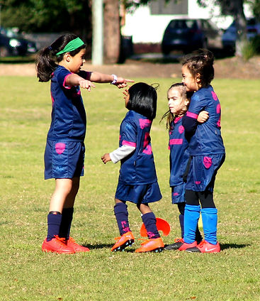 Three young girls in blue and pink soccer uniform being direct by tallest girl