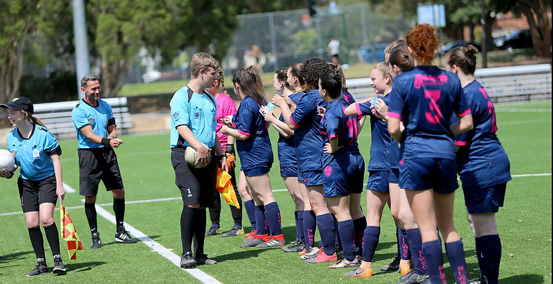 Young female soccer team in blue and pink uniform talking to young male umpire