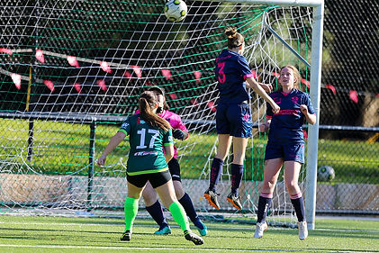 Women's soccer game in goal square with members jumping in front of net