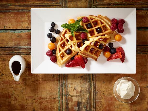 Waffles de la casa con sirope de maple, fresas frescas y salsa de yogurt y miel